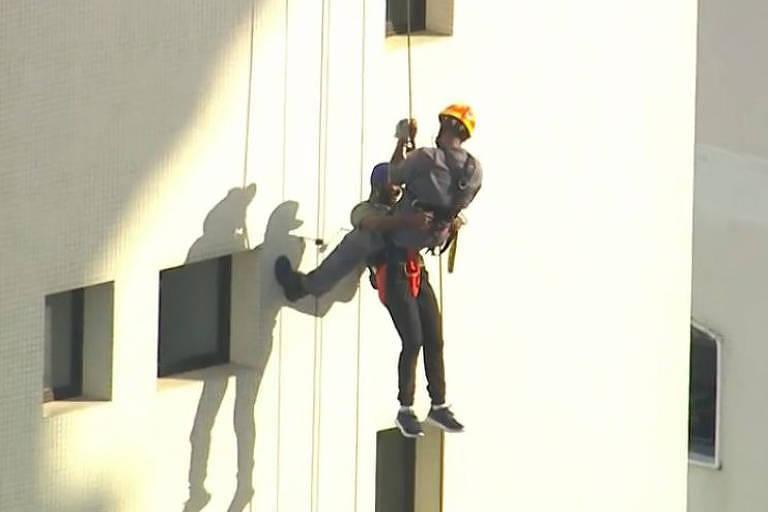 Ladrão foge de ônibus, invade prédio e fica pendurado em cabo
